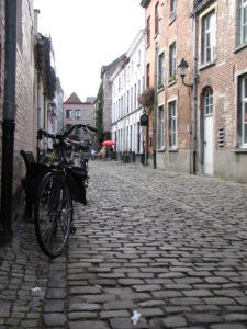 Cobblestone street in Gent with bicycles and outdoor patio